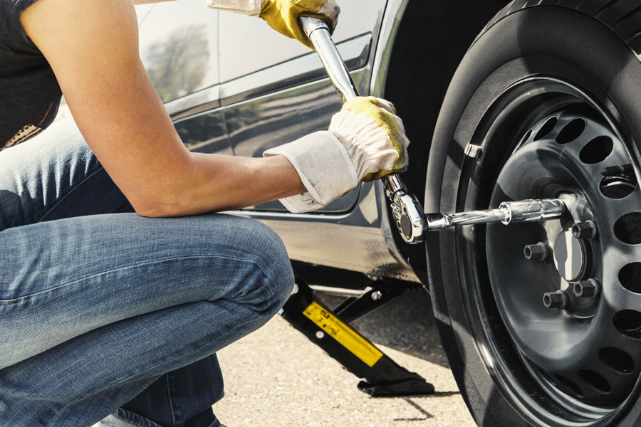 Woman changes tire with wrench